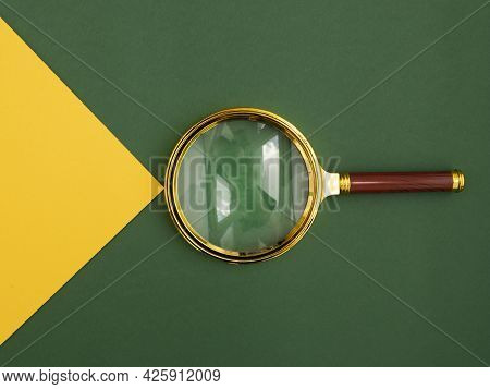 Magnifying Glass Over Green Background With Yellow Paper Beam As Symbol Of Insight, Discovery And Fi