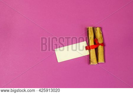 Dog Treats And Sales Tag On Pink Background. Air Dried Pet Sticks. Bully Sticks. Beef Pizzle. Tag Is