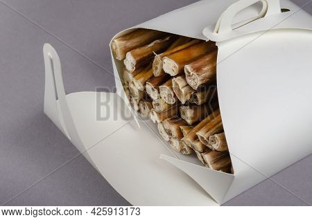 Pet Treats In A In A White Paper Box On A Gray Background. Dried Bully Sticks For Dogs. Beef Pizzle