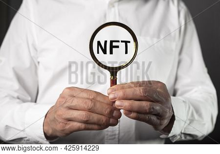 Nft Acronym In Male Hands Through Magnifier.