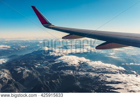 View From An Airplane To Jet Wing And Norwegian Fjords Landscape. Aircraft Flying Over Norway Scandi