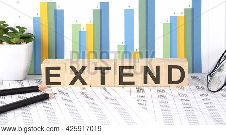 Extend Word Written On Wood Block With Chart, Glasses And Pencils
