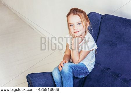 Sweet Little Girl In Jeans And White T-shirt Sitting On Modern Cozy Blue Chair Relaxing In White Bri