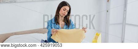 Dissatisfied Woman In Silk Pajama Looking At T-shirt Near Shopping Bags In Bedroom, Banner.