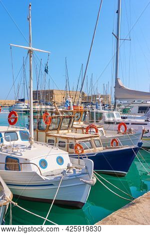 Colorful old fishing boats and yachts in the Venetian Harbor of Heraklion, Crete Island, Greece