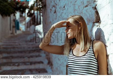 Portrait of a Nice Blond Female Looking Away. Waiting for Someone in Bright Sunny Day. Enjoying Travel to Greece.