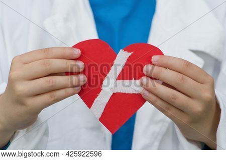 A Doctor Holds Red Paper Heart Stuck With Plaster.concept On The Theme Of Heart Disease, Surgery And