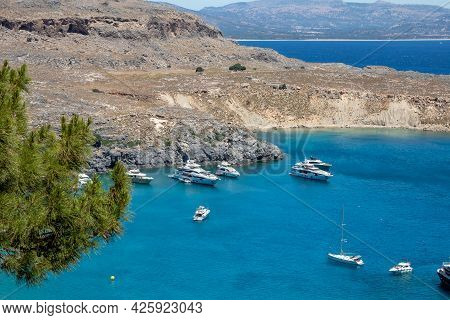 Lindos, Greece - Jun 05, 2021. View From The Acropolis In Lindos Of A Beautiful Lagoon With Boats An