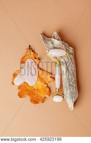 Chinese Gua Sha Stones, Wooden Root, Autumn Fall Leaves And Neautral Beige Background.  River Jade S
