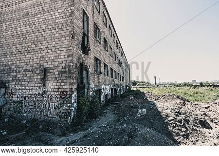 A Toned Image Of Part Of An Abandoned Red Brick Factory Building With Broken Glass. Destruction Conc