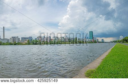 View Of The Frankfurt Skyline From The Banks Of The Main River During An Approaching Thunderstorm