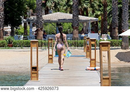 Tropical Vacation On Sea Resort. View To Girl With Scuba Mask Walking On Wooden Pier On Palm Trees A