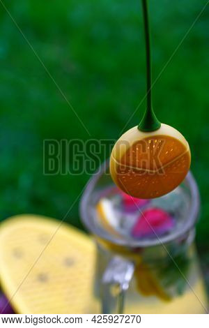Defocus Dummy Lemon Hanging Over Glass Jug Of Lemonade With Slice Lemon And Leaves Of Mint On Natura