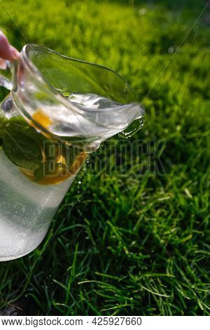 Defocus Pouring Glass Jug Of Lemonade With Lemon And Mint In On Natural Green Background. Drops Of W