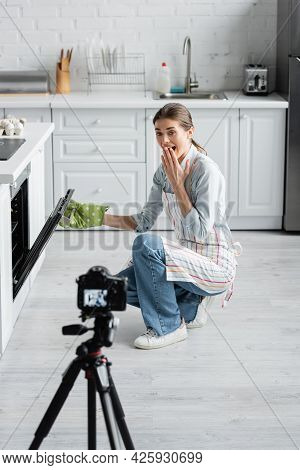 Astonished Culinary Blogger Covering Mouth While Opening Oven Near Blurred Digital Camera.