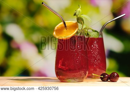 Summer Bar, Refreshing Drinks Concept. Cherry Cocktails Made Of Gin And Cherry Juice Decorated Orang