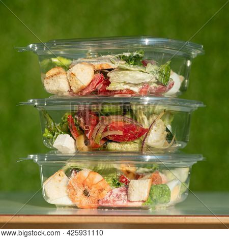 Ready-to-eat Food, Three Transparent Plastic Containers With Salads On Green Background. Tower From