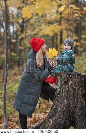 Mom And Baby On A Walk In The Autumn Park, Bright Warm Clothes, Leaf Fall Season