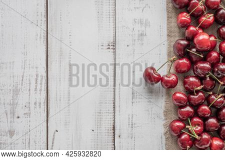 Berry Background On A Wooden Table, Ripe Berries On The Right, Top View, Framing With Red  Sweet Che