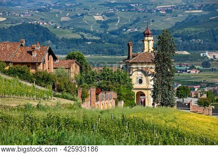View of green field, houses and church in small town of Guarene in Piedmont, Northern Italy.