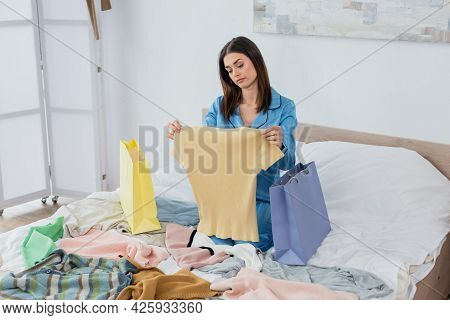 Displeased Woman In Silk Pajama Looking At T-shirt Near Shopping Bags And Plenty Of Clothes In Bedro