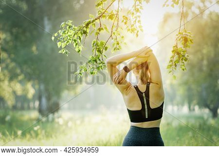 Rearview Shot Of A Sporty Adult Woman Stretching Her Arms While Exercising Outdoors.