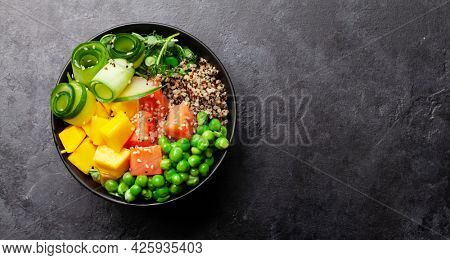 Poke bowl with salmon, cucumber and mango. Traditional hawaiian meal. Top view flat lay with copy space