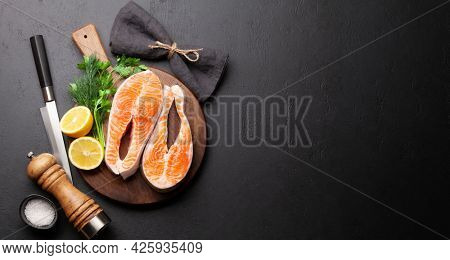 Fresh raw salmon cooking. Fish steaks with herbs and spices. Top view flat lay with copy space