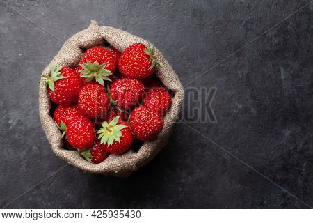 Strawberry in burlap bag. Ripe garden berries on stone table. Top view flat lay with copy space