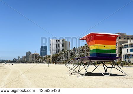 LONG BEACH, CALIF - 5 JUL 2021: Pride Tower, at Shoreline Way and 12th Pl, with the city skyline in the background. The rainbow-colored lifeguard tower supports the LGBTQ community.