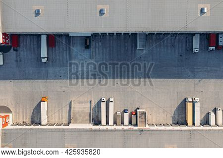 Trucks With Trailers Wait For The Loading Of Goods For Transportation In The Loading Warehouse. Aeri