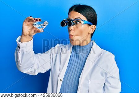 Beautiful brunette jeweller woman holding brilliant diamond stone wearing magnifier glasses making fish face with mouth and squinting eyes, crazy and comical.