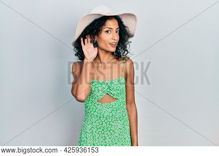 Young latin girl wearing summer hat smiling with hand over ear listening an hearing to rumor or gossip. deafness concept.