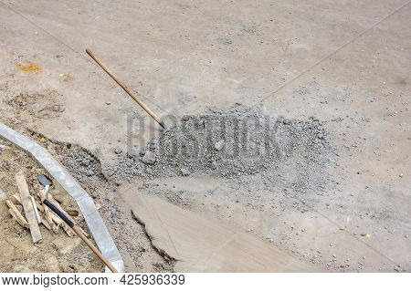 Old Iron Shovel With A Wooden Handle In A Pile Of Rubble At A Construction Site