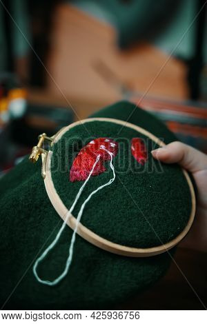 Woman Hands Doing Stitch. Close Up Of Embroidery Of Mushroom Hat In Wooden Hoop On Green Material. C