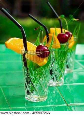 Refreshing Drinks In Crystal Glasses Leaves Cherry Orange Slice Green Tile Background Shadow Sweet C