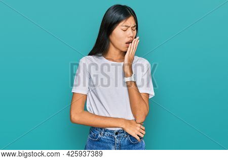 Beautiful young asian woman wearing casual white t shirt bored yawning tired covering mouth with hand. restless and sleepiness.