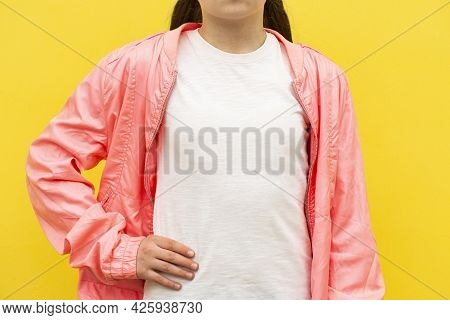 Mockup Of White Cotton T-shirt. Teenage Girl In White T-shirt And Pink Jacket Stands Against Pink Wa