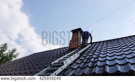 A Man Climbs A Metal Ladder To The Roof Of The Bathhouse To Clean The Pipe From Soot And Soot