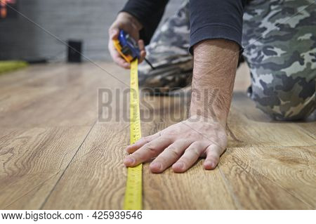 Repair, Building And Home Concept - Close Up Of Male Hands Measuring Wood Flooring. Laying Laminate