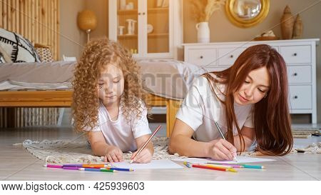 Concentrated Mother And Preschooler Daughter With Long Loose Hair Draw On Papers With Colourful Penc