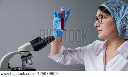 Skilled Female Scientist With Spectacles Looks At Sample Of Red Liquid In Test Tube Near Microscope