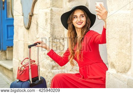 Beautiful Young Caucasian Woman In Black Hat Smiling And Sitting On Stairs At The Door Outdoors