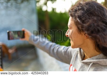 A Young Girl Blogger Takes Pictures Of Herself With A Phone. Blogger's Video Report.