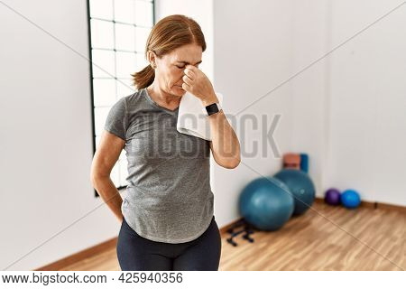 Middle age woman wearing sporty look training at the gym room tired rubbing nose and eyes feeling fatigue and headache. stress and frustration concept.