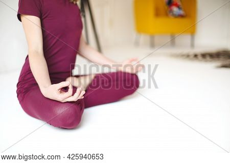 Back View Of Unrecognizable Female In Sportswear Sitting With Crossed Legs And Mudra Hands On Mat An