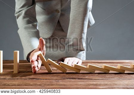Close Up Female Hand Interrupting Domino Effect. Operative Business Solution, Strategy And Successfu