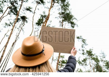 Female Hands Standing With Cardboard Outdoors. Nature Background. Copy Space For Text Sustainable Li