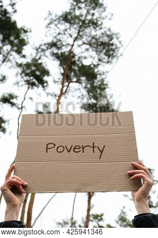 Female Hands Holding Cardboard With Text Poverty Outdoors. Nature Background. Protester Activist. So