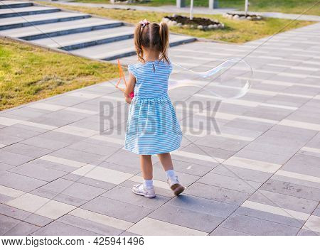 In A Public Park, A Little Girl Blows And Catches Soap Bubbles.the Child Is Playing And Laughing. Th